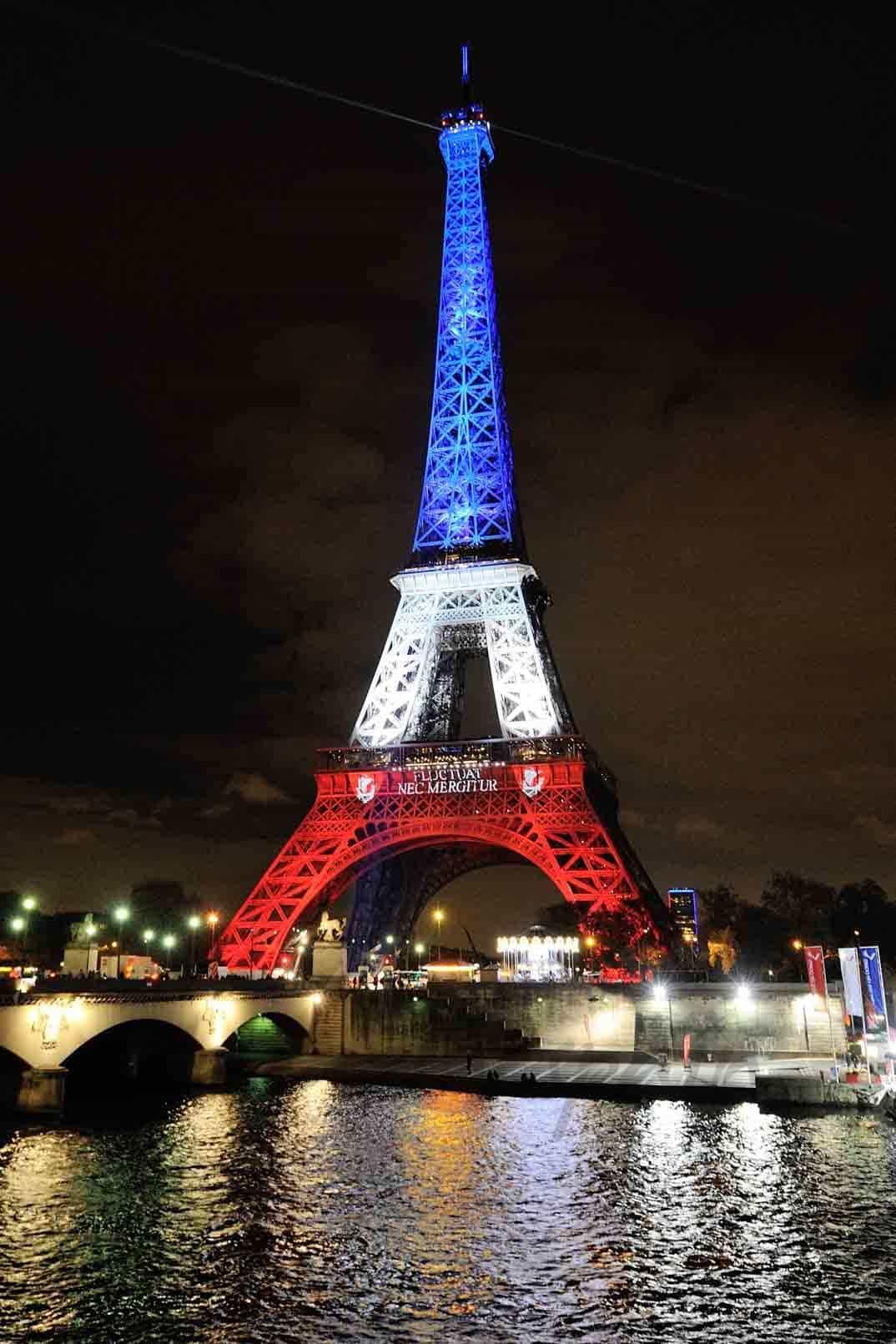 torre eiffel iluminada con los colores de la bandera francesa